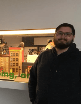 A man wearing glasses and a black sweatshirt smiles in front of a window display of buildings.