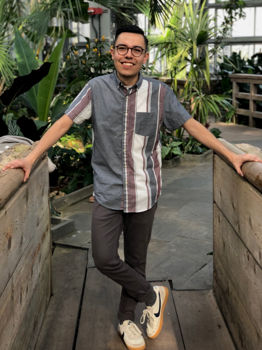 Young man with glasses, short sleeved collared shirt, and tennis shoes stands smiling on a wooden foot bridge with trees behind him