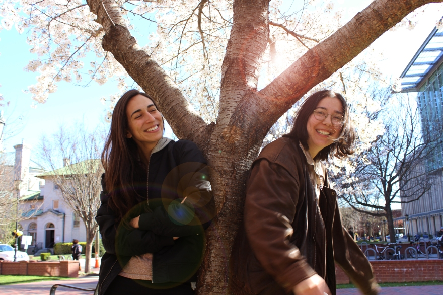 Two girls smiling leaning against a tree trunk in the middle of VCU campus