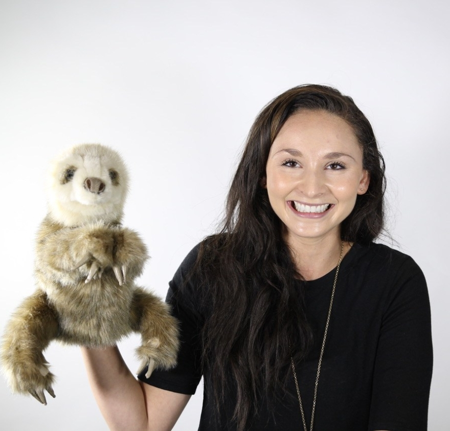 A girl in black with long dark hair smiles while holding up a stuffed animal sloth puppet on a white background.